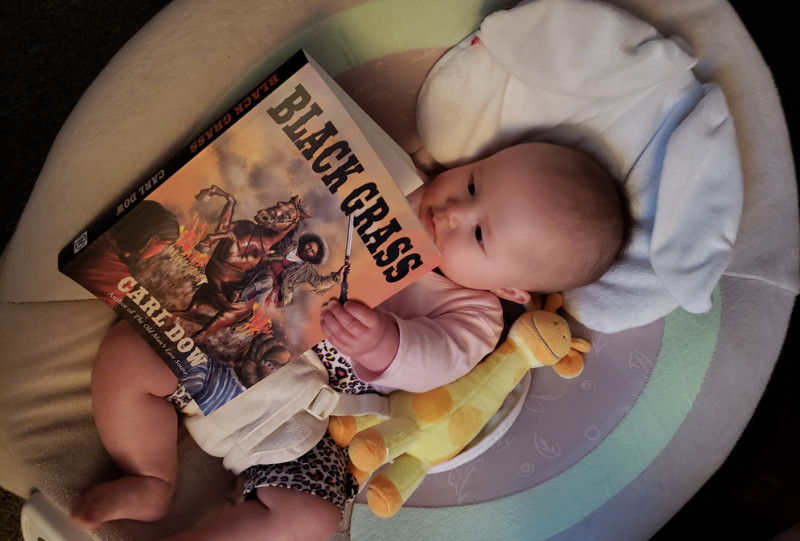 My sweet baby holds a copy of my father's sweet book, Black Grass